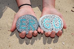 Hände halten Seite mit ERGO Aufschrift vor Sand