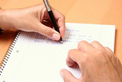 Ergotherapie: Linkshänder schreibst mit Stift auf Papierblock