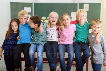 lachende kinder in der grundschule sitzen auf dem tisch, gruppentherapie