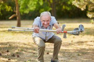Glücklicher Senior macht Kniebeuge mit Krücken in seinen Händen