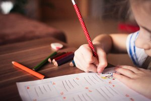 Kinderhand hält Stift und malt