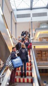 Kolleginnen auf Rolltreppe mit Gepäck und Firmenkleidung