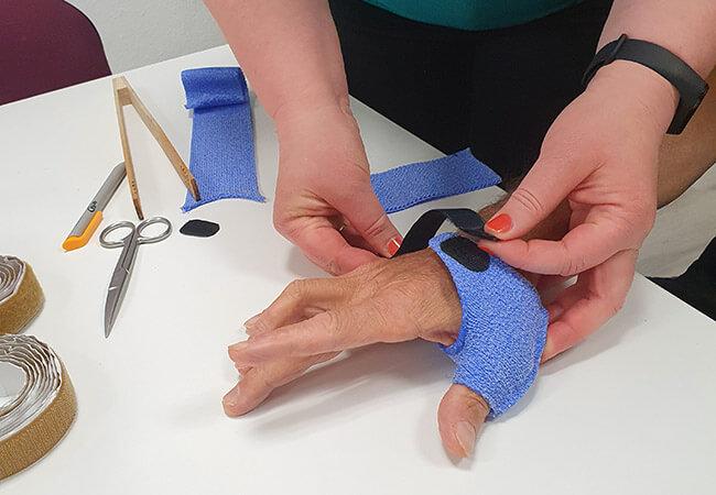 Ergotherapeutin legt Patienten Schiene an