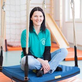 Ergotherapeutin Julia Walter auf einer Therapieschaukel im Motorikraum